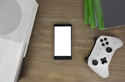 View from the top on smart phone, game console, game pad, game discs and game accessorize. Laying on the table. You can put any image on a screen Royalty Free Stock Photography