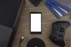 View from the top on smart phone, game console, game pad, game discs and game accessorize. Laying on the table. You can put any image on a screen Stock Photo