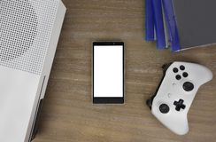 View from the top on smart phone, game console, game pad, game discs and game accessorize. Laying on the table. You can put any image on a screen Royalty Free Stock Photos