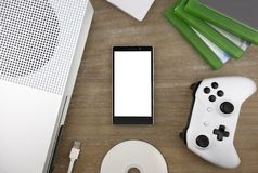 View from the top on smart phone, game console, game pad, game discs and game accessorize. Laying on the table. You can put any image on a screen Royalty Free Stock Images