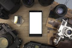 View from the top on smartphone of photographer, photos, cameras and photo accessorize. Laying on the table. You can put any image on a screen Stock Photography