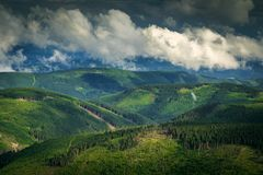Background landscape of a wide area of green hills coverd with forest and clouds. View from the top of Snezka Mountain, showing a wide landscape of green hills Stock Images