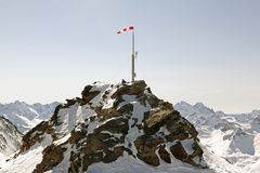 A view of the top of a snowy mountain and a wind flag and a security camera on it in the alps switzerland.  Royalty Free Stock Image