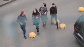 View from top on street where four stylish people walk. Two girls and two men cross the road. Slow mo, steadicam shot. View down on the street where four young stock footage