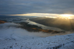 View from the top. The sun sets on Loch Lomond, Scotland.  Taken from the top of Ben Lomond Royalty Free Stock Image