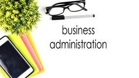VIEW FROM THE TOP, TABLE WORKING WITH TEXT `BUSINESS ADMINISTRATION` Stock Photo