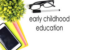 VIEW FROM THE TOP, TABLE WORKING WITH TEXT `EARLY CHILDHOOD EDUCATION` Stock Photos