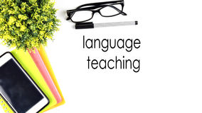 VIEW FROM THE TOP, TABLE WORKING WITH TEXT `LANGUAGE TEACHING`. White background work desk with notebook, glasses, tree ornaments, pen and smartphone Stock Photos