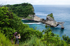 View from top to Atuh Beach, Nusa Penida Bali, Indonesia with person taking a photo of the bay Royalty Free Stock Images