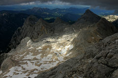 View from the top of Triglav to Zeleni Sneg. View from the top of Triglav, to bucket glacier Zeleni Sneg and dark clouds threatening with sun spots Stock Photo