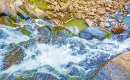 View from the top of the waterfall falling down, forest landscape with a waterfall, where begins the descent to water. Royalty Free Stock Photo