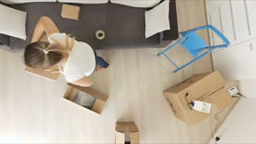 View from the top on young couple carrying boxes in new apartment. View from top on young couple carrying boxes in new apartment stock video footage