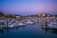 View of Torquay harbor at dusk, South Devon, UK. TORQUAY, DEVON UK - OCTOBER 14, 2017: View of the harbor in Torquay. Torquay, a seaside town in Devon, also Stock Photos