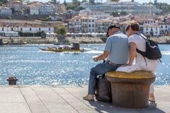 View of tourist senior couple seating on concrete bench on Ribeira docks stock images