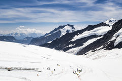 View of tourists and Aletsch glacier from Jungfraujoch, Switzerland. Group of tourists enjoy activities on Jungfraujoch Royalty Free Stock Photos