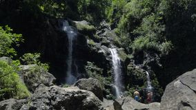 Tourists in front of the Upper Waikani Falls. View of tourists in front of the Upper Waikani Falls stock footage
