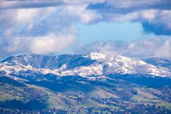 View towards Mt Hamilton and the Lick Observatory building on a sunny winter day; green hills in the foreground and snow covered stock photo