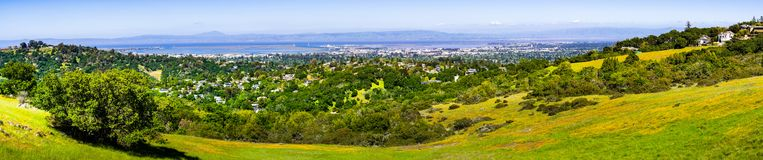 View towards Redwood City and Menlo Park; hills and valleys covered in green grass and wildflowers visible in the foreground, stock images