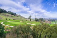 View towards Santa Teresa Golf Course from the trails of Santa Teresa County Park; a group of friends are gathered around a hole; royalty free stock photos