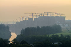 View of tower cranes at construction of public housing residential blocks with river canal along the estate. Royalty Free Stock Photo