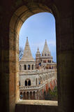 View on towers of Fisherman`s Bastion through an arch. View on the numerous towers of Fisherman`s Bastion on a winter day through an arch window. Budapest Stock Photos
