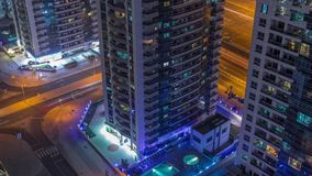 View of various skyscrapers and towers in Dubai Marina from above aerial night timelapse. View of towers with swimming pool and traffic on intersection in Dubai stock video