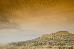 View of the town of mardin with tobacco sky. A view of the ancient town on Mardin sitting on a hilltop in a desert landscape with a tobacco sky Royalty Free Stock Images