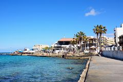 View of the town and sea, Mellieha. Pavement cafes in the harbour with boats in dry dock to the rear, Mellieha, Malta, Europe Stock Images