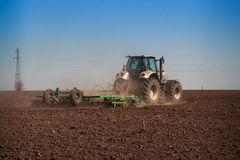 View of tractor seeder sowing in ploughed field Royalty Free Stock Photos