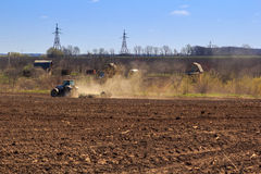 view of tractor sowing in field in early spring Stock Photo
