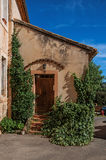 View of traditional colorful house in ocher and bindweed under a sunny blue sky, in Roussillon Royalty Free Stock Photos