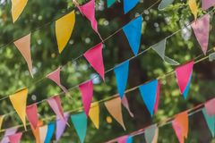 View of traditional decoration of popular festivals of the villages, with colored triangles of paper hanging in threads, blurred. Tree as background, in stock image