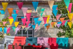 View of traditional decoration of popular festivals of the villages, with colored triangles of paper hanging in threads, classic. House and vegetation as stock photos