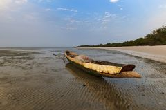 View of a traditional fishing canoe at the beach in the island of Orango at sunset, in Guinea Bissau. Orango is part of the Bijagos Archipelago; Concept for stock photography