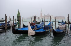 View of traditional Gondolas on Canal Grande in Venice Venezia in a foggy day with San Giorgio Island on the background, Italy royalty free stock images
