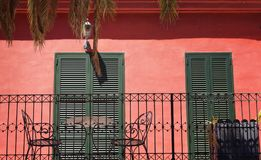 View of a traditional Mallarco house. View of a traditional Mallorca house. Red wall, green shutters and iron made chairs / table reflect style of region`s Stock Photos