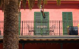 View of a traditional Mallorca house. Red wall, green shutters and iron made chairs / table reflect style of region`s architecture Royalty Free Stock Photography