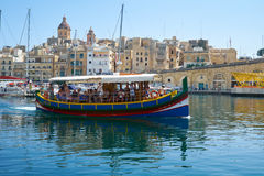 The view of traditional Maltese boat Luzzu in Dockyard bay on th. BIRGU, MALTA - JULY 23, 2015: The view of traditional Maltese boat Luzzu, serving as a walking Stock Images