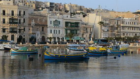 The view on traditional Maltese boats in sunset stock footage