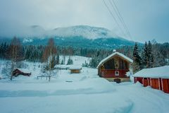 View of traditional Norwegian mountain red wooden houses covered with snow in stunning nature background in Norway.  Royalty Free Stock Photography