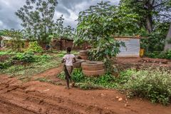 View of traditional village, backs of a child walking. Malange / Angola - 12 08 2018: View of traditional village, backs of a child walking, tropical vegetation royalty free stock photos