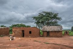 View of traditional village, thatched houses on roof and terracotta brick walls, kids playing outside, cloudy sky as background stock image