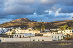 View on traditional whitewashed village with volcanos on the bac Stock Image