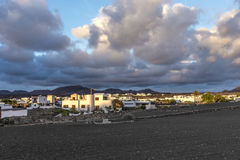 View on traditional whitewashed village with volcanos on the bac Royalty Free Stock Images