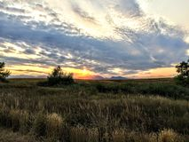 View from Trail near Josh`s Pond in Broomfield Colorado at Sunset reflecting off water, Rocky Mountains in the background Stock Image