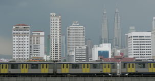 View of train on the foreground and modern buildings skyscraper on the background. Kuala Lumpur, Malaysia. View of riding train on railways on the foreground and stock footage