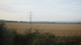View from train - High voltage tower in a wheat field at sunny day. Autumn, Europe stock video