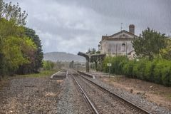 View of train line, rainy day, Obidos train station as background. In Portugal raining water rainfall exterior outside building classical vernacular stock photos