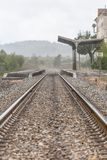 View of train line, rainy day, Obidos train station as background. In Portugal raining water rainfall exterior outside building classical vernacular stock image