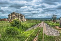 View of the train line, ruined house and tropical vegetation, cloudy background. In Angola royalty free stock photo